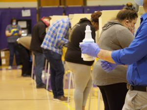 poll worker holds up cleaning solution in front of voters wearing masks